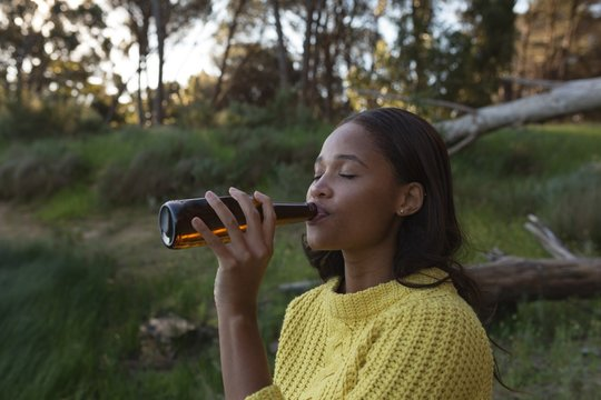 Woman drinking beer in forest