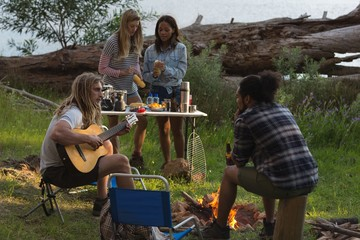 Group of friends having fun near bonfire
