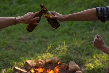 Men toasting beer bottle near campfire