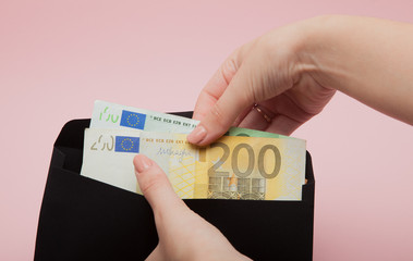 Women hands put euro in black envelope on pink background.Business Concept and Instagram