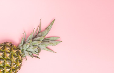 Half cut juicy pineapple on a pastel pink background. Minimal summer concept