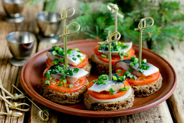 Canapes with rye bread, salted herring fillet, mustard, onion, tomato and skewers on plate