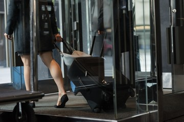Businesswoman leaving hotel with luggage
