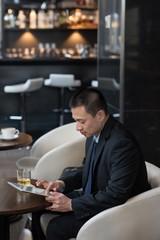 Businessman using digital tablet on sofa