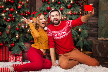 Happy family couple in love with santa and elf hats warm sweaters doing selfie with smartphone for greeting parents with Merry Christmas and Happy 2019 New Year at home with decorated christmas tree