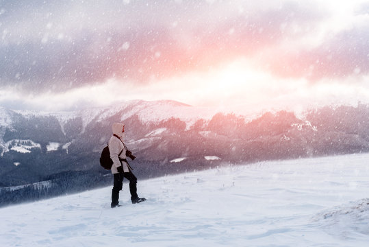 Alone photographer on mountain top in snowstorm with a backpack in winter time. Travel concept. Carpathian mountains. Landscape photography