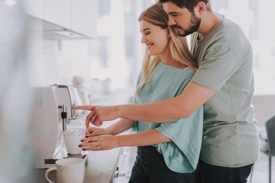 Waist up photo of happy woman and man making coffee with machine at home