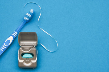 Dental floss and toothbrush on a blue background with copy space