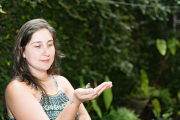 Mulher segurando pequeno beija-flor verde nas mão, desfoque.