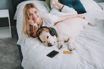Delighted smiling beautiful woman lying in bed while having fun with her dog with headphones