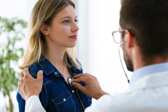 Handsome young male doctor checking beautiful young woman patient heartbeat using stethoscope in medical office.