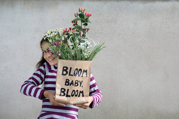 Smiling girl holding paper bag with flowers