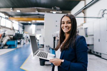 Confident woman working in high tech enterprise, holding laptop