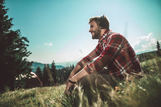 Relaxing in travel with good sounds. Side on low angle portrait of bearded cheerful male sitting on green mountain hill and listening music by mobile phone