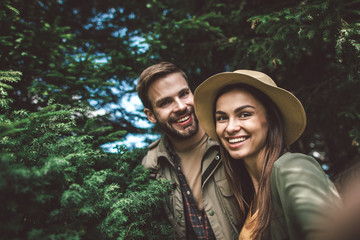 Concept of enjoying journey and adventure in couple. Close up portrait of happy smiling man and woman making selfie in sunny green forest