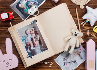 Open album with picture near accessories on wooden background
