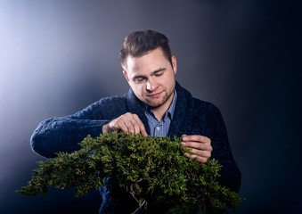 Studio shot of young man pruning japanese bonsai tree.