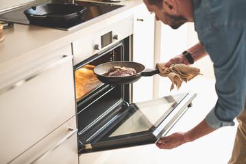 Gentleman holding frying pan with beef steak while opening oven door