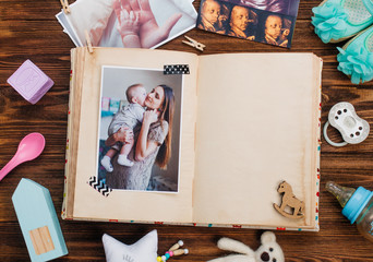 Open album with picture near accessories on wooden background with copy space
