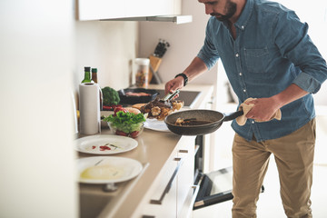 Cropped portrait of gentleman in denim shirt holding frying pan and tongs with beef steak