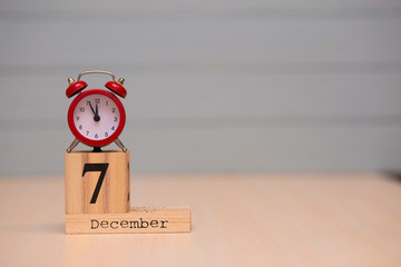 December 7th set on wooden calendar and red alarm clock with blue background.