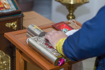 priest hand on bible with cross