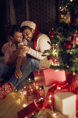 couple and present by Christmas tree