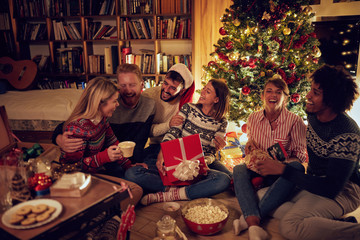smiling frineds together by Christmas tree