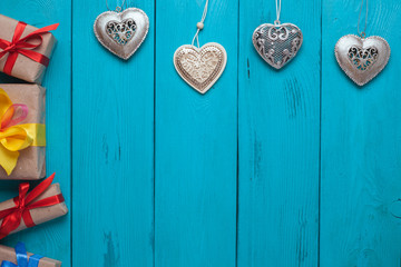 Turquoise background for Christmas cards. Background for Christmas wishes. Blue wooden planks. Vintage background for congratulation. Holiday gift. Hearts of silver as an element of Christmas decor.