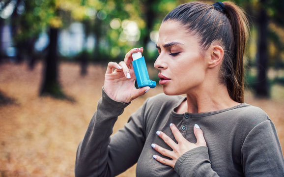 Young woman treating asthma with inhaler