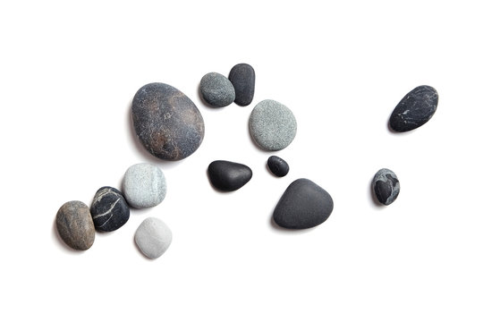 Scattered sea pebbles. Smooth gray and black stones isolated on white background. Top view