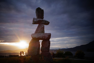 Silhouette of people watching the sunset near the Inuksuk Inuit rock statue in Vancouver, British Columbia Fototapete