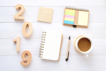 2019 wood letters, blank notebook paper and coffee on white table background, 2019 new year mock up, template with copy space for text, top view