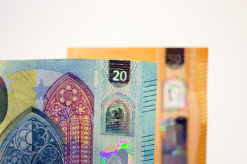 closeup of new banknote of twenty euros with another fifty bill, out of focus in the background.