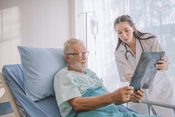 Doctor showing X-ray to patient, elder men felt worried about result from a nurse