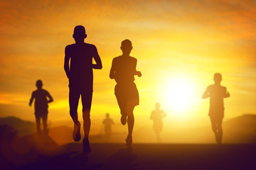 silhouette of a lot of people running marathon in sunset on the way