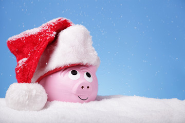 Piggy bank in snow wearing a Santa hat Wall mural
