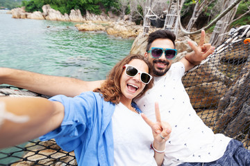 Young beautiful happy smiling funny couple man and woman best friends on a hammock on vacation makes selfie on a smartphone against the background of the sea