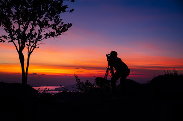 Silhouette Young man photographer taking nature photo on PhraYa Dern Thong mountain landscape.province Lopburi.Thailand. tourist photographe shooting dslr camera on tripod