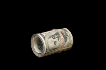 A roll of one hundred dollar bills tied with a rope. On a black background. Isolated