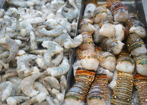 Raw lobster tail and shrimp frozen on the ice for sale