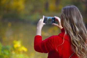 a girl in a red sweater takes pictures on a smartphone