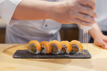 Preparation sushi roll in restaurant, close up chef hands. Japanese food.