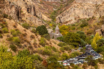 View of the road through the mountains and pilgrims at the monastery of Geghard in the rocks of Geghama ridge in Armenia