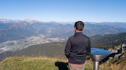 Person is looking at the Alps from the summit of the mountain