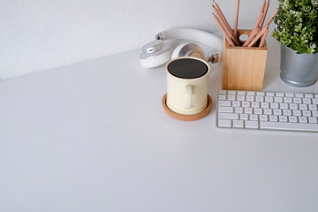 Office desk coffee mug, computer keyboard, pencil and headphone on table.
