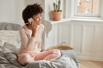 Photo of Afro American lady makes appointment via cellular, dressed in casual clothes, sits in lotus pose on bed, wears casual clothes, enjoys conversation with friends, has day off, poses in bedroom