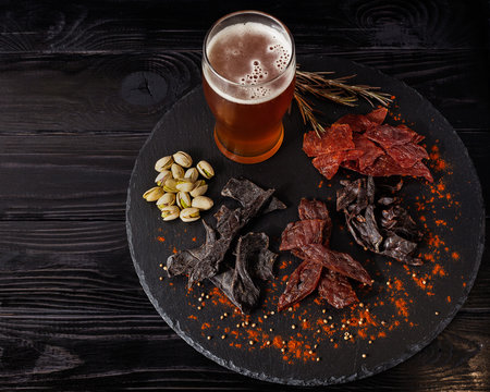 Assorted snacks, jerky on circle stone board with cold beer