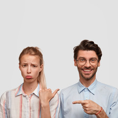 Wall Mural - Vertical shot of dissatisfied blonde woman purses lower lip, being offended by guy. Positive unshaven hipster with pleasant smile, points at girlfriend, isolated over white background, free space