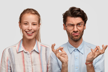 Wall Mural - Photo of smiling light haired woman, expresses happiness, discontent unshaven man with gloomy expression, raises eyebrows in dislike, spreads hands, isolated over white background. Emotions, reaction